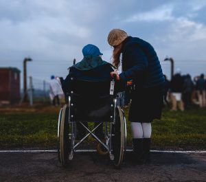 Back view of person leaving over person in wheelchair